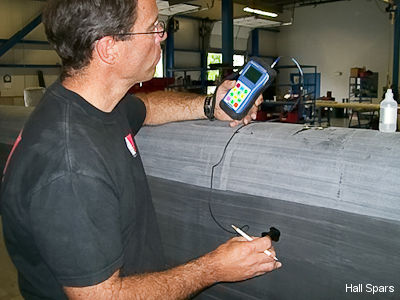 An Halls Spars engineer inspects a carbon fibre mast using an ultrasound machine.