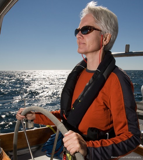"Phyllis Nickel at the helm of ""Morgan's Cloud"" during a sunny windy afternoon sail off Jonesport, Maine."