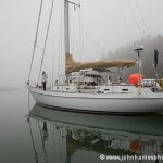 Aluminum sailboat Morgan's Cloud at anchor in the fog in the Mud Hole, Downeast Maine.