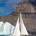 Aluminum expedition sailboat Morgan's Cloud underway in front of an iceberg and mountain at Uummannaq, West Greenland.