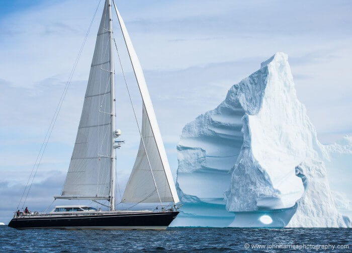 Vivid, a Jongert 27 sailobat, sails in front of an iceberg in Disko Bay, Greenland.