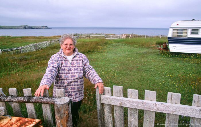 Genevieve from Bonavista, Newfoundland stands at the gate of her summer place.