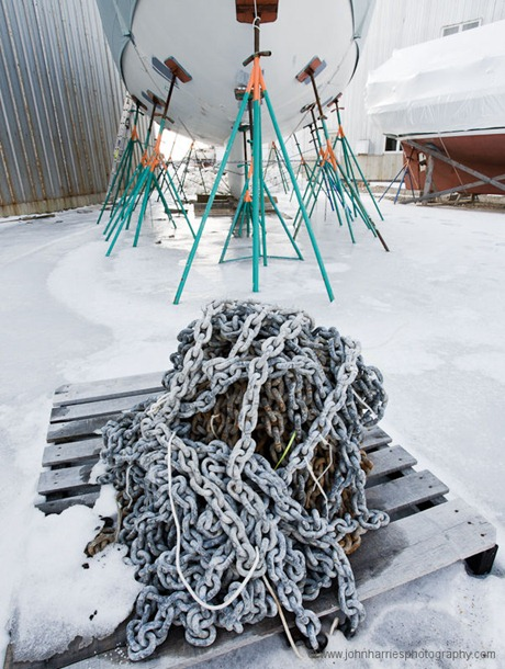 """""""Morgan's Cloud"""" on the hard at Billings Diesel and Marine in Stonington, Maine, with a pile of anchor chain frozen to a pallet at her bow during one of the three winters we spent at Billings refitting the boat."""