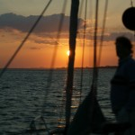 Woman on bow of sailboat at sunset
