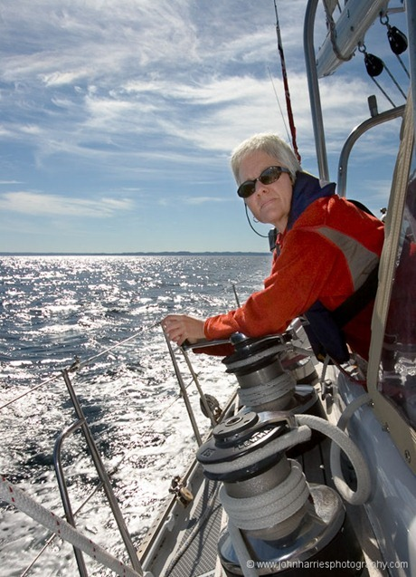 Phyllis Nickel takes a turn on the jib sheet during a sunny summer afternoon off the east coast of Newfoundland, Canada.