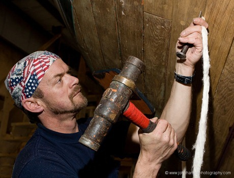 Dale Haley, model release available, caulks the bottom of a restored wooden sloop at Billings Diesel and Marine