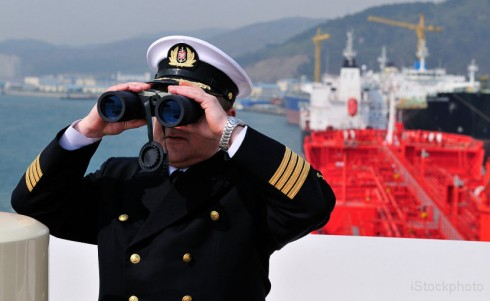 A captain looking through binoculars on the deck of a ship.